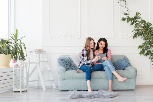 Women sitting together on sofa and watching something in tablet Free Photo