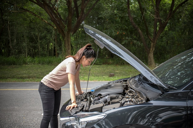 Women spection she opened the hood broken car on the side see engines that are damaged or not Premium Photo