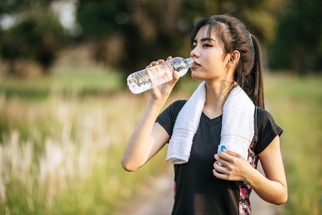 女性は運動後に水を飲むために立ちます 無料写真