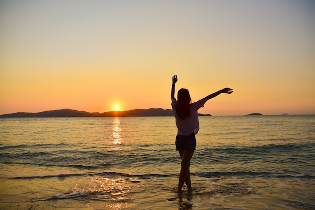 Women standing on beach at sea sunset background on evening