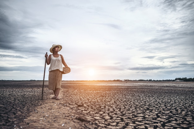 Women standing on dry soil and fishing gear, global warming and water crisis Free Photo