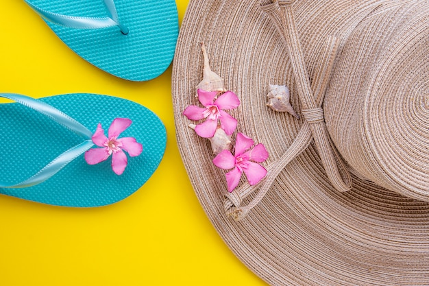 Women straw hat with bow pink tropical flowers blue slippers sea shells on yellow background Premium Photo