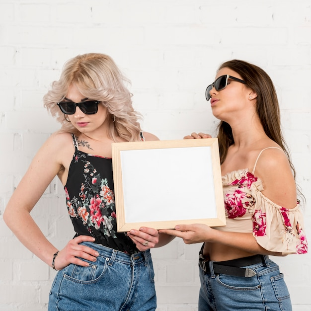 Women in sunglasses holding empty paper in hands Free Photo