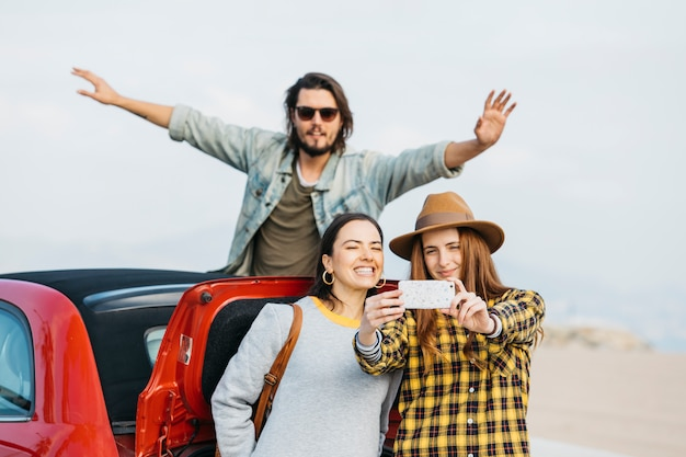 Women taking selfie on smartphone near car trunk and man leaning out from auto Free Photo