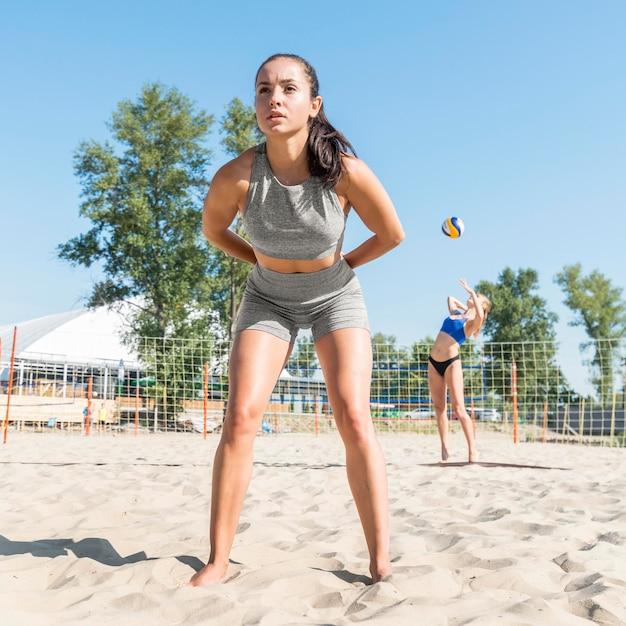 Compagne di squadra di donne che giocano a pallavolo sulla spiaggia Foto Gratuite
