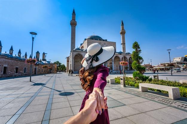 男性の手を握り、トルコのコンヤにあるモスクに彼を導く女性観光客。 無料写真