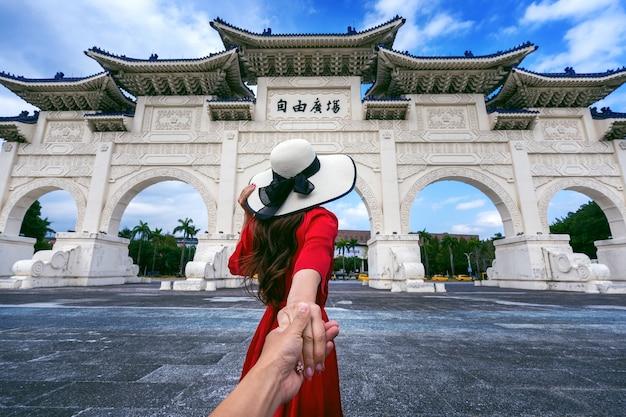 Women tourists holding man's hand and leading him to chiang kai shek memorial hall in taipei, taiwan. Free Photo