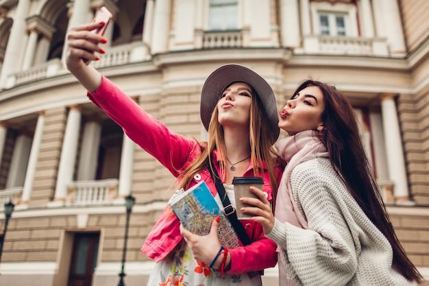 Women tourists taking selfie going sightseeing in odessa. happy friends travelers having fun Premium Photo