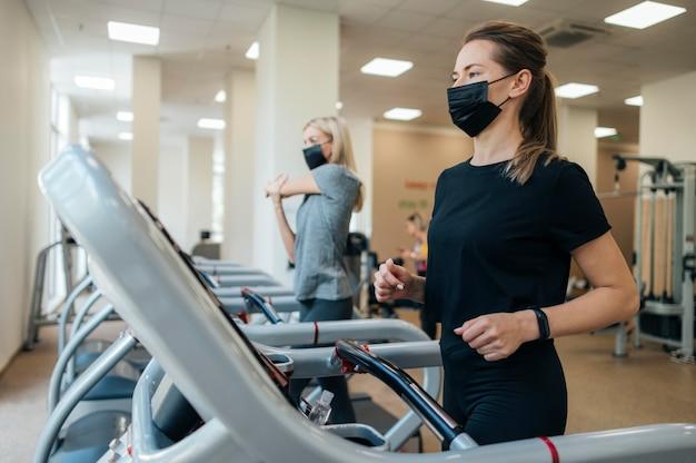 대유행 기간 동안 체육관에서 훈련하는 여성 프리미엄 사진