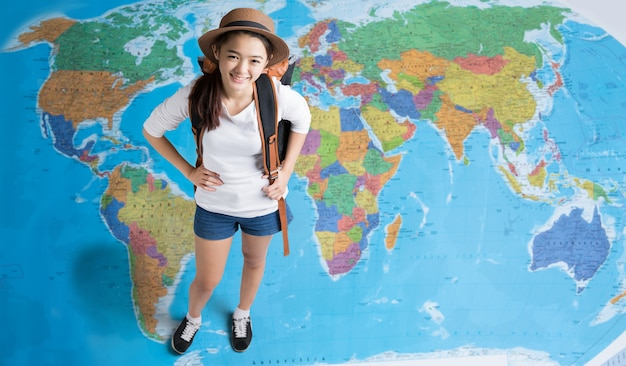 Women traveler is planning a tour of asia, her standing on the world map Premium Photo