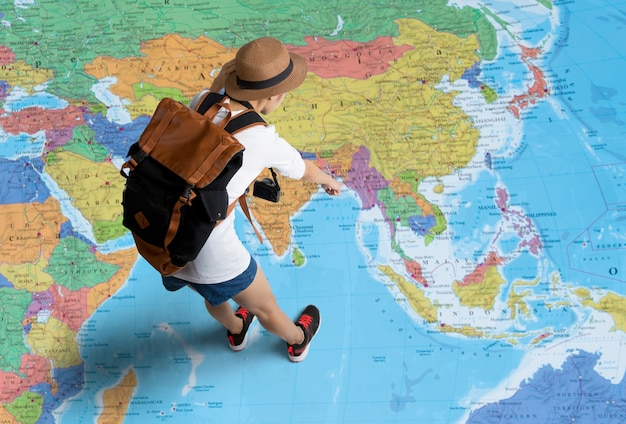 Women traveler is planning a tour her standing on the world map.she points to the map Premium Photo