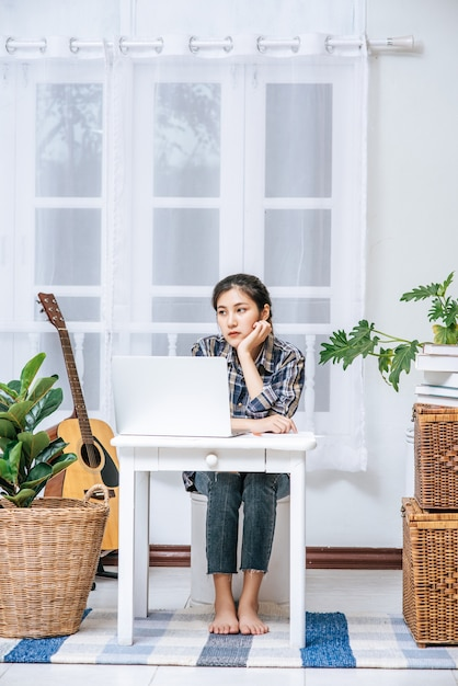 Women use a laptop at their desks and are stressed. Free Photo