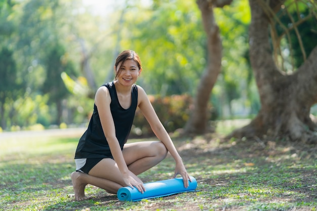 Women use rolling yoga mat to do exercises yoga in the park, sport yoga concept Premium Photo