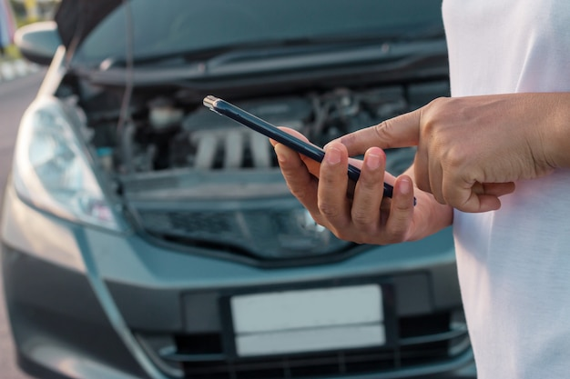 Women using mobile phone to take pictures of her car that opens the hood. Premium Photo