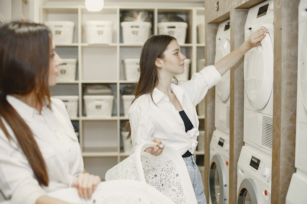 Women using washing machine doing the laundry. young girls ready to wash clothes. interior, washing process concept Free Photo