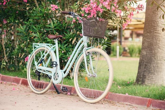緑の茂みとピンクの花に対して女性のビンテージ自転車。路上駐車のバスケットが付いているスタイリッシュなレトロな自転車。 Premium写真