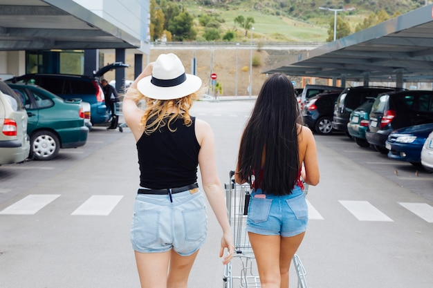 Women walking to car with products in shopping trolley from supermarket Free Photo