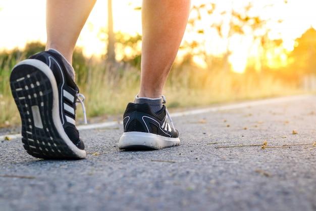 太陽のオレンジ色の光を見て、夕方には運動を歩いている女性 Premium写真