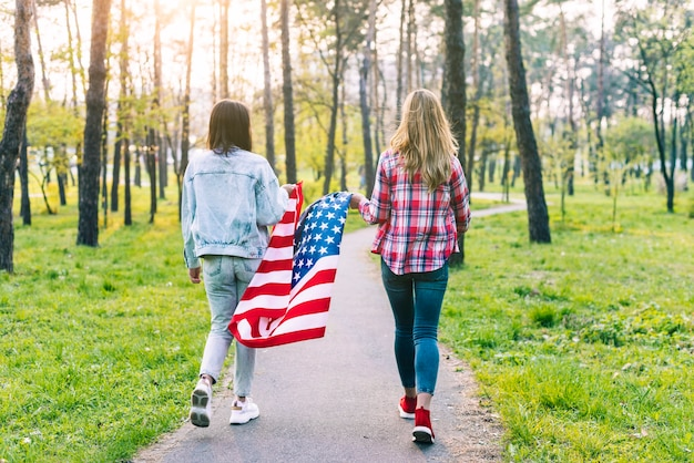 Women walking in park with usa flag Free Photo