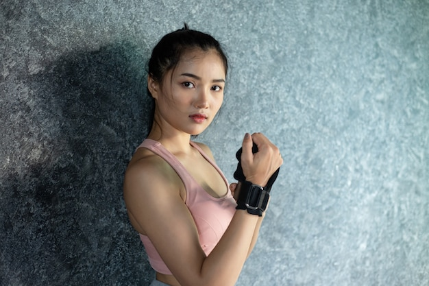 Women wear wristbands to exercise and stand against the wall. Free Photo