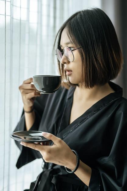 黒いローブを着て、寝室でコーヒーを渡す女性。 無料写真