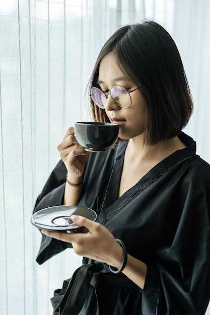 Женщины в черных халатах, раздают кофе в спальне. Бесплатные Фотографии