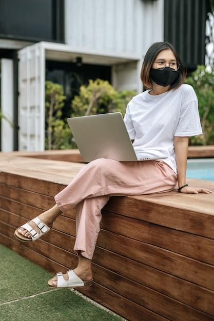 マスクをしてプールサイドでラップトップをする女性。 無料写真
