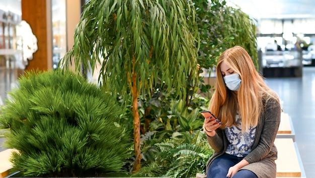 マスクを身に着けている女性は、電話で、間隔を空けてソーシャルでショッピングモールに座っています。 Premium写真
