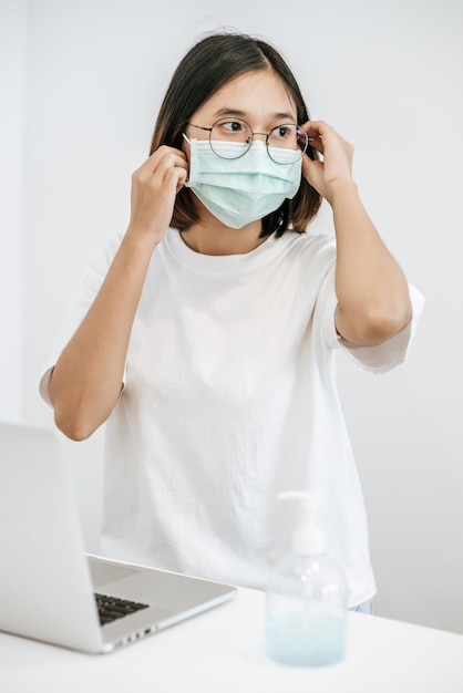 Women wearing sanitary masks have a laptop on the table and hand washing gel. Free Photo