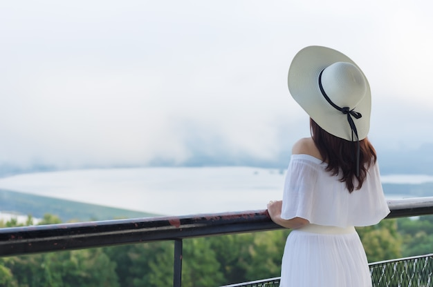Women wearing a white brimmed hat standing back to watch the view. Premium Photo