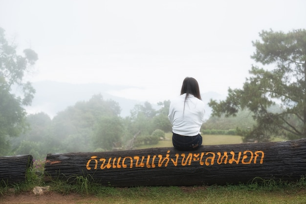 Women wearing a white shirt sitting on a stick,looking at the sea of fog Premium Photo