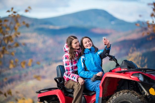 Women in winter jackets on red quad bike Premium Photo