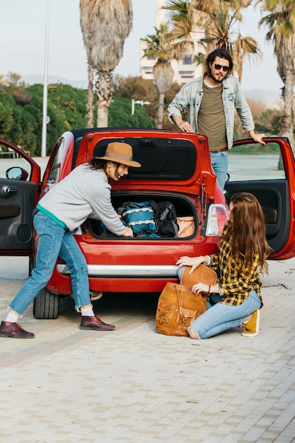 Women with backpack near car trunk and man leaning out from car Free Photo