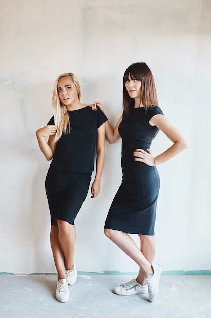 Women with black dress posing on wall Free Photo
