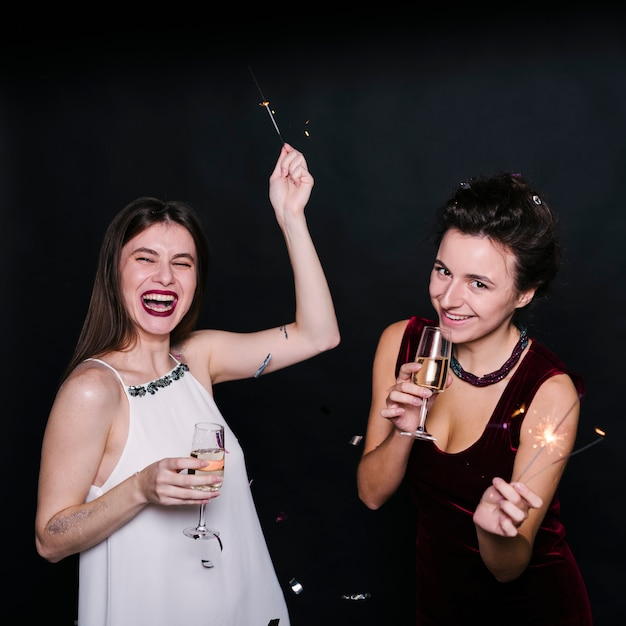 Women with glasses of champagne and sparklers Free Photo