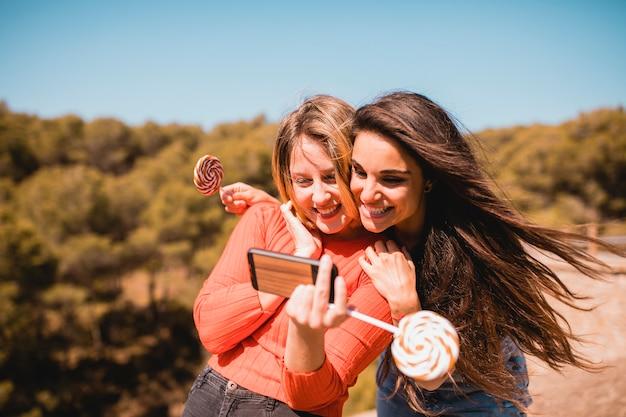 Women with lollipops taking selfie Free Photo