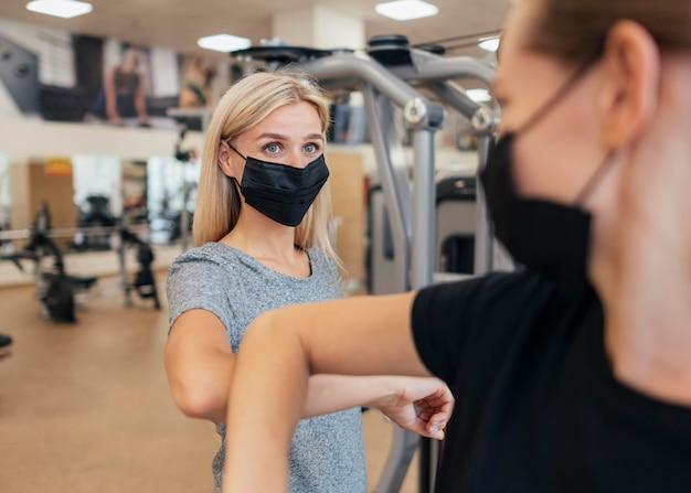 Женщины в медицинских масках практикуют приветствие локтем в тренажерном зале Бесплатные Фотографии