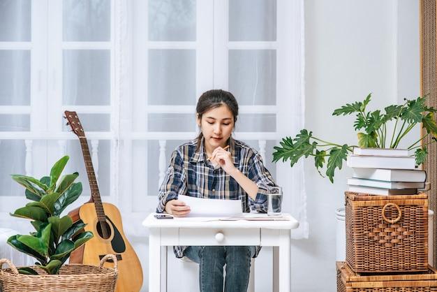 女性はテーブルで働き、文書を分析します。 無料写真