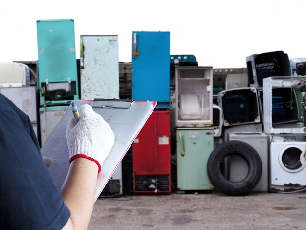 Women work in recycling garbage plant electronics washing machine waste old, used and obsolete electronic equipment for  recycle in factory industry. Premium Photo
