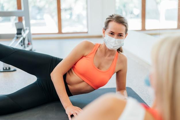 Женщины, работающие в тренажерном зале вместе с медицинской маской Бесплатные Фотографии
