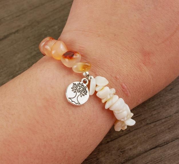 Women wrist wearing beaded bracelet on wooden background Premium Photo