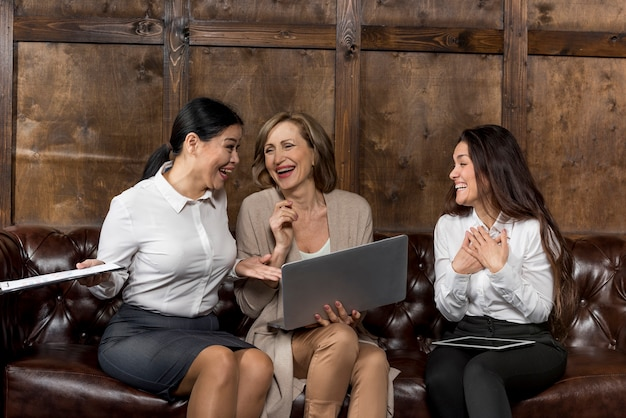 Womens on couch having a good laugh Free Photo