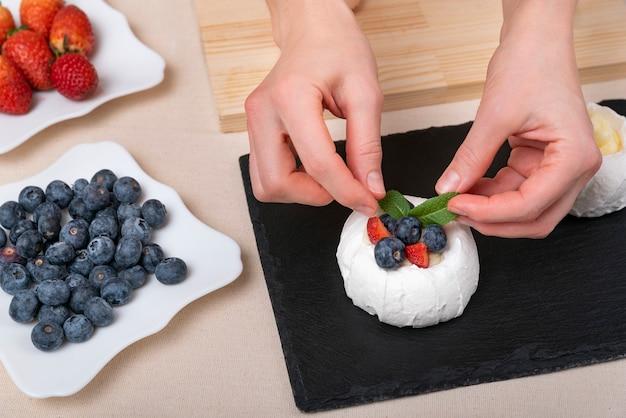 Женские руки украшают торт. свежие ягоды и вид сверху торт. Premium Фотографии