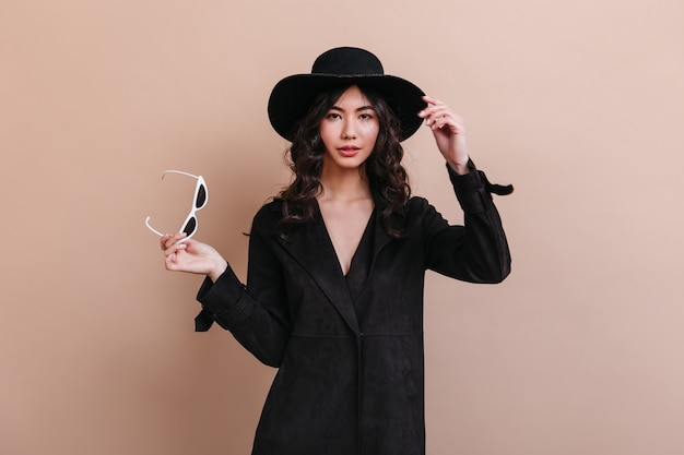 Wonderful asian woman in coat holding sunglasses. front view of well-dressed korean woman isolated on beige background. Free Photo