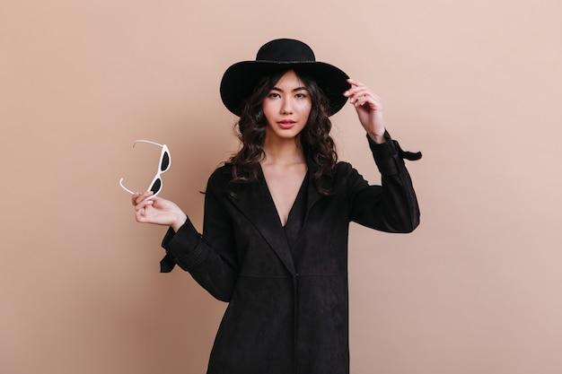 サングラスを保持しているコートの素晴らしいアジアの女性。ベージュの背景で隔離の身なりのよい韓国人女性の正面図。 無料写真