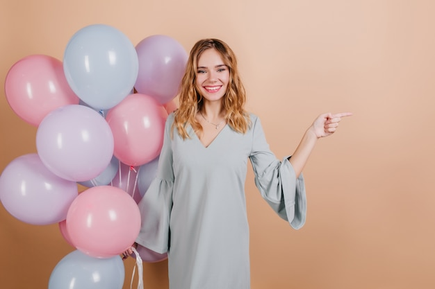 미소로 포즈를 취하고 밝은 풍선을 들고 멋진 생일 여자 무료 사진