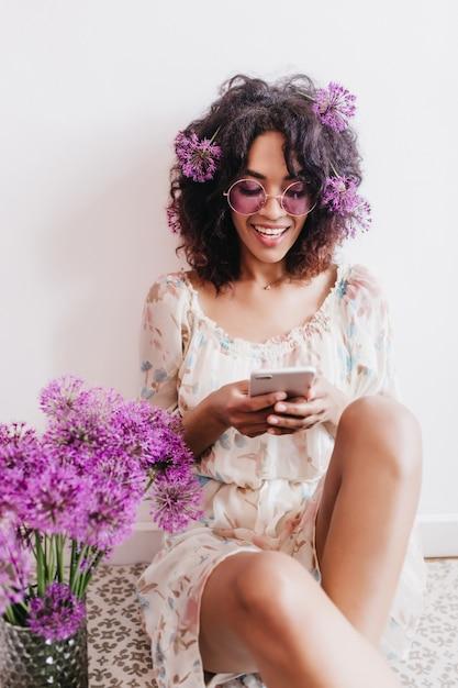 Meraviglioso messaggio di sms di donna bruna nera con sorriso. tiro al coperto di bella ragazza africana seduta accanto al bouquet di allium. Foto Gratuite