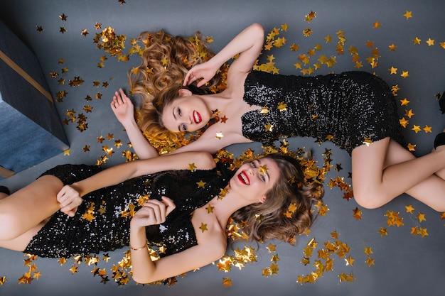 Замечательная темноволосая девушка в черном платье лежит под конфетти и смеется с сестрой. крытый портрет милых дам в роскошных нарядах, наслаждающихся фотосессией на вечеринке. Бесплатные Фотографии