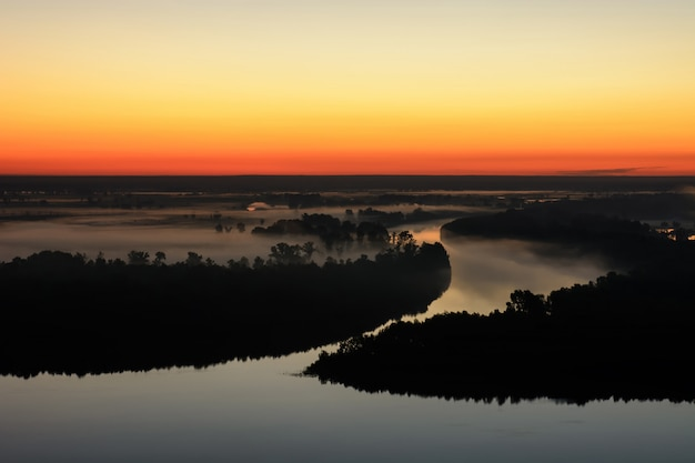 Wonderful ghostly foggy dawn above silhouette of island and misty river. Premium Photo