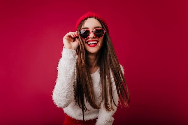 Splendida ragazza in bicchieri di cuore alla moda che esprimono buone emozioni Foto Gratuite